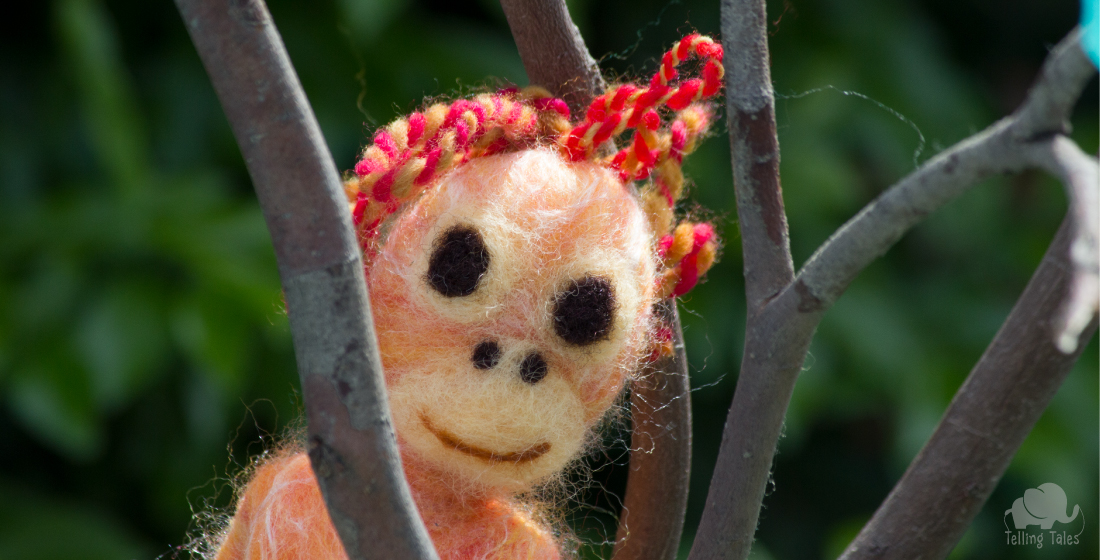 Felted baby orangutan marionette peeking through branches
