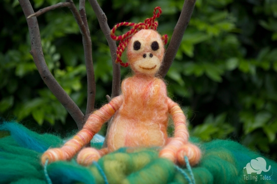 Lily, the orangutan felted marionette sitting on a fern